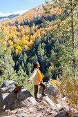 Frau in Wanderkleidung steht mit ausgestreckten Armen auf Felsvorsprung in herbstlicher Berglandschaft