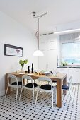 Solid wooden table and white retro chairs in modern kitchen with white and grey mosaic floor tiles