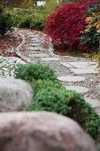Round stepping stones in gravel path leading through Japanese garden