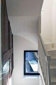 Weisses Treppenhaus mit Wendeltreppe und Wandpaneel