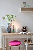 Hocker mit, pinkfarbenem Kissen und Stuhl vor ländlichem Schreibtisch