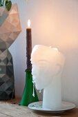 Aus Wachs geformter Kopf als Kerze neben Kerzenhalter mit brennender Kerze