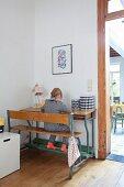 Kleines Mädchen an Tisch-Bankkombination vor Wand, neben teilweise sichtbaren Durchgang
