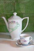 Kaffeekanne und Tasse mit Untertasse mit Blumenmotiv vor grünen Wandfliesen