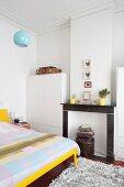 Bett mit gelbem Bettgestell, Bettwäsche in Patchwork Muster, gegenüber ehemaliger Kamin zwischen weissen Schränken