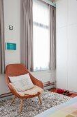 Brauner Ledersessel auf flokatiartigen Teppich vor Fenster mit hellgrauem Vorhang