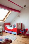 Kinderzimmer unter dem Dach, Klassiker Schaukelstuhl mit roter Sitzschale neben Schlittenbett in Rot