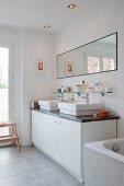 Moderne Waschtischzeile mit weissem Unterschrank und zwei Aufbaubecken an Wand mit breitem Spiegel