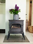 Bouquet of lilac in zinc pot on top of vintage, log-burning stove