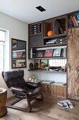 Vintage Sessel mit Lederbezug vor selbstgebauter Regalwand mit rustikalen Holzelementen