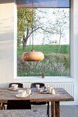 Rustikaler Holztisch, Schalenstühle und Retroleuchte vor Panoramafenster mit Gartenblick