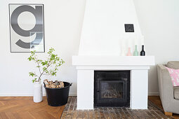Open fireplace, logs in bucket and white vase of leafy branches below framed typographical poster