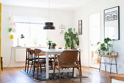 Retro chairs with wooden frames around white dining table below pendant lamp in front of house plants next to window
