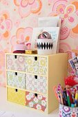 Miniature chest of drawers with floral wallpaper on front and pot of writing utensils against retro floral wallpaper