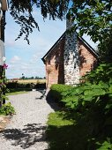 Sunny gravel garden path leading to simple brick house with external chimney