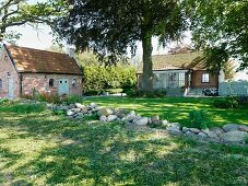 Boulders in garden with summer house and brick country house in background