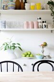 Dining table, black chairs, fruit bowl on sideboard and wall-mounted shelves