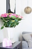 White vase of pink hydrangeas on side table
