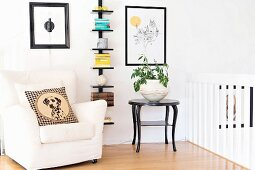 Cushion with dog motif on white armchair, potted plant on black side table and stacked books on wall-mounted shelves