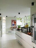 Offene Küche mit moderner Küchenzeile, im Hintergrund Essplatz zwischen Terrassentüren