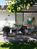 Geflechtstühle in Graubraun um Tisch auf Holzterrasse, vor zeitgenössischem Wohnhaus