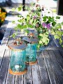Zwei Vintage Laternen und Fliederstrauss auf Holztisch