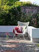 White wicker armchair and striped cushion on gravel terrace surrounded by low white wall