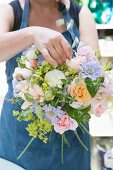 Woman typing bouquet of roses and scabious