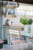 Blue and white country-house kitchen with wooden table and wall-mounted shelves