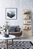 Shelf leaning against the wall, sofa with pillows, carpet with black and white pattern