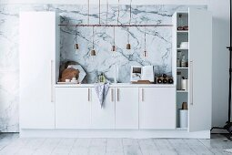 White kitchenette with tall cupboards, integrated counter, row of pendant lamps with cords wrapped around rod and marbled effect on wall