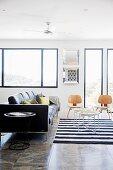 Travertinfliesen in Wohnraum mit Ledersofa, Repliken von Klassikerstühlen aus Holz und Tabletttischen auf gestreiftem Webteppich