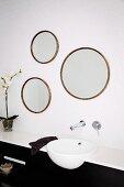Aus alten, runden Bilderrahmen selbstgefertigtes Spiegeltrio über modernem Waschbecken mit Wandarmatur auf weissen Mosaikfliesen