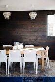 Stapelstühle und grosser Holztisch in Esszimmer mit Kristallleuchter, dunkler Holzwand und königsblauem Teppich auf Travertinboden