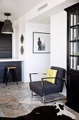 Elegant retro armchair with chrome steel frame and black industrial lamps above kitchen counter with vintage-style stool