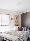 Embroidered wall hanging, vintage bedroom bench and wall painted a modern dark brown in bedroom