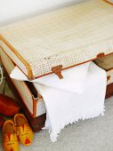 Pale vintage suitcase, white blanket and wooden clogs arranged on carpeted floor