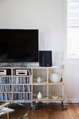 TV, speakers, CDs and vases on open-fronted vintage shelving on castors