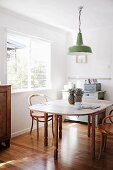 Extendible wooden dining table, wooden chairs, green retro pendant lamp, vintage cabinet and glossy parquet floor