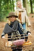 Mother and daughter having autumn picnic in woods