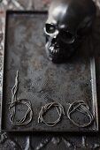 Skull and lettering reading 'boo' made from noodles on metal tray