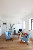 Sessel- und Sofagarnitur im 50er Jahre Stil mit hellblauem Bezug und filigraner Couchtisch aus Holz auf Holzboden in minimalistischem Ambiente