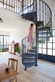 Frau auf gusseiserner Wendeltreppe in offenem Wohnraum