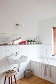 Badezimmerecke mit weissen U-Bahnfliesen, Hocker und Waschbecken im Fiftiesstil