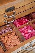 Unterteilte, offene Schublade mit farbigen Knöpfen