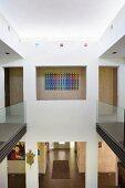 Blick von der Galerie mit Glasbrüstungen in den Eingangsbereich eines Architektenhauses