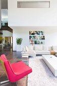 Luxuswohnung mit pinkfarbenem Polstersessel und offenem Galerie-Wohnbereich