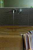 Eleganter Holzwaschtisch mit eingearbeitetem Waschbecken und gestreiftem Handtuch, Wandarmatur mit Wasserstrahl