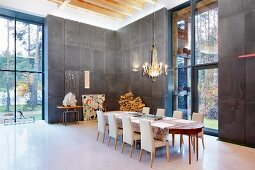 Chandelier above long dining table with upholstered chairs in double-height interior with charcoal-grey wall panels and tall windows
