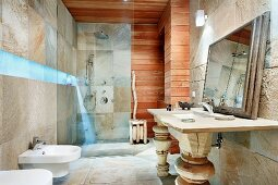 Bathroom with blue lighting strip between stone-tiled walls and horizontal wooden cladding, washstand with carved wooden legs and framed mirror